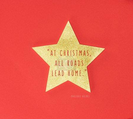 """Photo pour Étoile dorée avec """"à Noël toutes les routes mènent à la maison"""" inspiration isolée sur fond rouge - image libre de droit"""