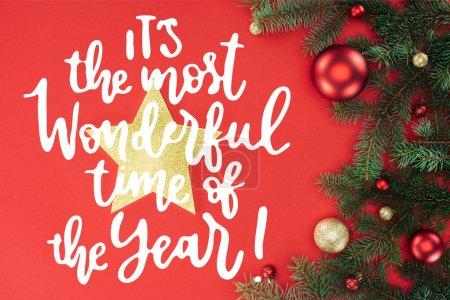 Photo pour Lay plat avec des branches d'arbre de pin avec des boules de Noël rouges et dorées et étoile d'or isolées sur rouge avec inspiration «c'est le plus beau moment de l'année» - image libre de droit