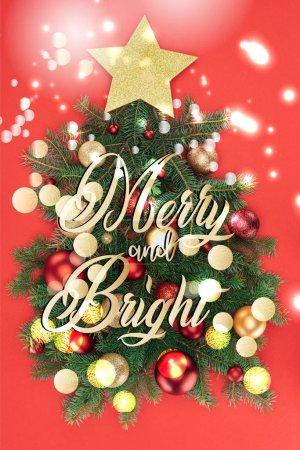 Photo pour Vue de dessus des branches d'arbres de pin, golden star et boules de Noël disposées en sapin isolé sur rouge avec lumières de lettrage et bokeh «joyeux et lumineux» - image libre de droit