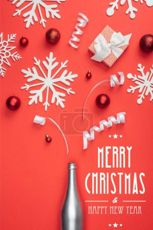 "Photo for Top view of present, champagne bottle, red christmas toys, white ribbons and decorative snowflakes arranged isolated on red with ""merry christmas and happy new year"" lettering - Royalty Free Image"