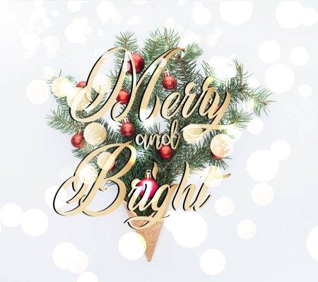 Photo pour Vue de dessus des jouets de Noël rouge sur des branches d'arbre de pin en cornet de crème glacée isolé sur blanc avec des lumières de lettrage et bokeh «joyeux et lumineux» - image libre de droit
