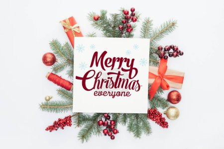 "Photo for Top view of pine tree branches, christmas decorations and gifts  with ""merry christmas everyone"" lettering in middle isolated on white - Royalty Free Image"