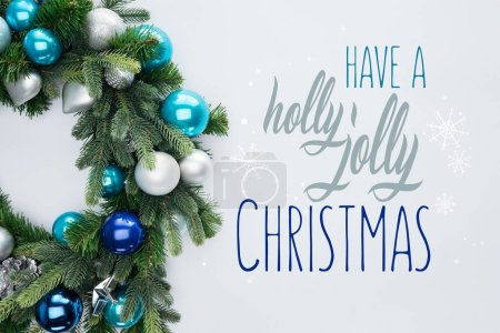 """top view of decorative festive wreath with blue and silver christmas toys isolated on white  with """"have a holly jolly christmas"""" inspiration"""