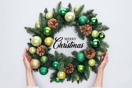 """Photo for Cropped shot of woman holding christmas wreath  with """"merry christmas"""" lettering isolated on white - Royalty Free Image"""
