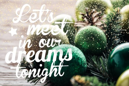 """Photo for Close up view of pine tree wreath with green christmas balls on wooden background with """"lets meet in our dreams tonight"""" inspiration - Royalty Free Image"""