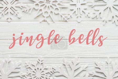 "Photo for Flat lay with decorative snowflakes on white wooden background with ""jingle bells"" lettering - Royalty Free Image"
