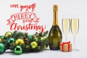 "bottle and glasses of champagne, christmas wreath and gift on white background with ""have yourself a merry little christmas"" inspiration"
