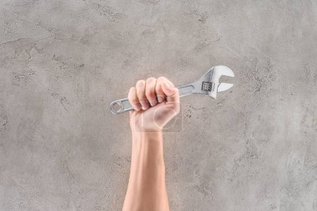 Photo pour Recadrée tir d'homme tenant clé à tuyau sur la surface du béton - image libre de droit