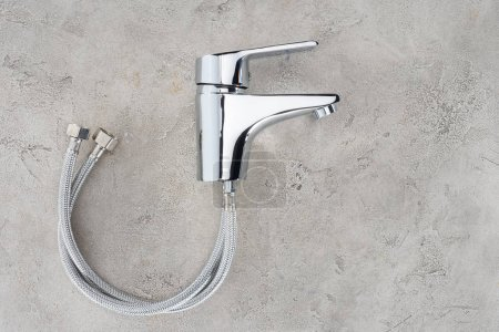 top view of water mixer with flexible pipes on concrete surface