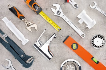 flat lay with various plumbing tools on concrete surface
