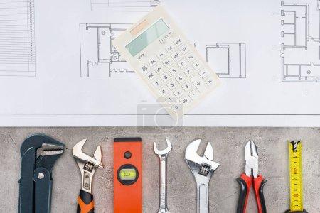 Foto de Vista superior del edificio plan con fila de diversas herramientas y calculadora en la superficie de hormigón - Imagen libre de derechos