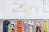 top view of building plan with row of various tools and calculator on concrete surface