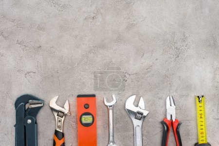 flat lay with row of various tools on concrete surface