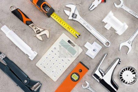 Foto de Lay Flat con diversas herramientas y calculadora en superficie de concreto - Imagen libre de derechos