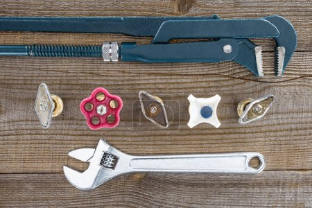 top view of plumber wrenches and various plumbing valves on rustic wooden tabletop