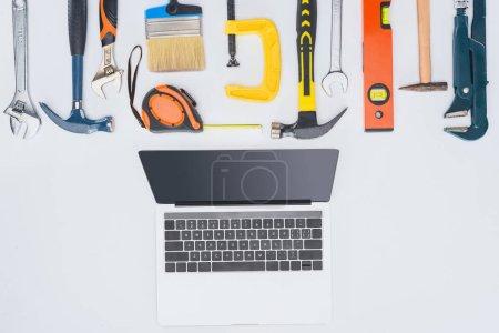 Foto de Vista superior de portátil con diferentes herramientas en blanco - Imagen libre de derechos