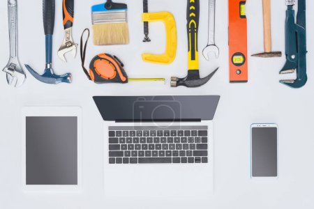 top view of laptop with various tools lying on white