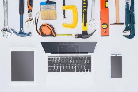 Foto de Vista superior de la portátil con varias herramientas en blanco - Imagen libre de derechos