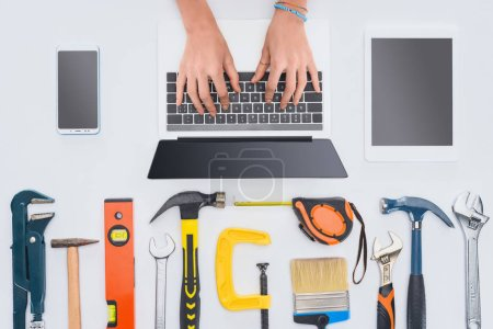 Photo for Cropped shot of woman using laptop with various tools lying on white - Royalty Free Image