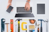 cropped shot of woman using devices with various tools lying on white