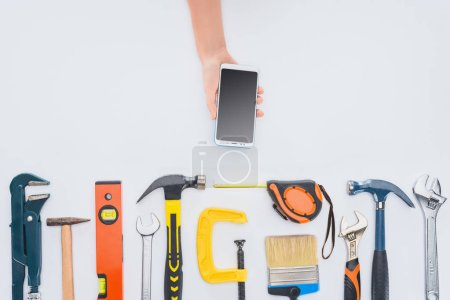Photo for Cropped shot of woman using smartphone with various tools lying on white - Royalty Free Image