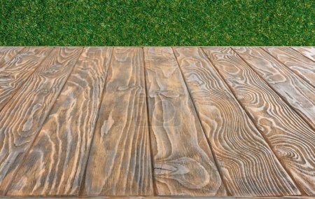 Photo for Surface of brown wooden planks on green grass background - Royalty Free Image