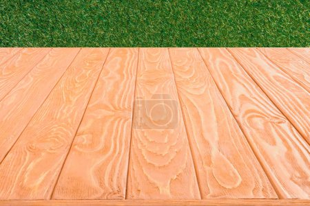 surface of orange wooden planks on green grass background