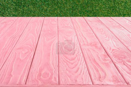 surface of pink wooden planks on green grass background