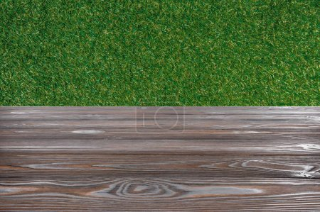 template of brown wooden floor with green grass on background