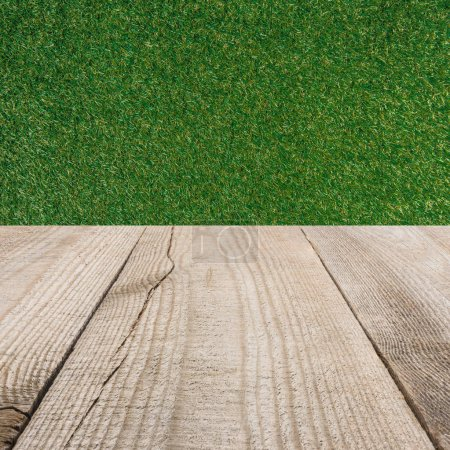 surface of beige wooden planks with green grass background