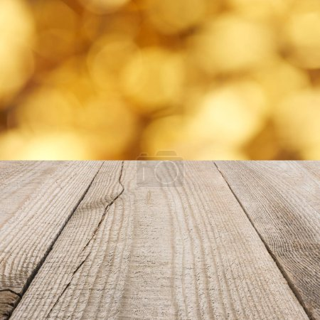 surface of beige wooden planks with blurry golden background