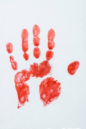 top view of blood print made with hand on white surface