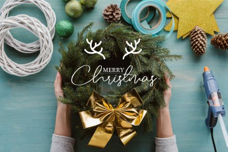 """cropped shot of woman holding handmade pine tree wreath with golden bow and decorations on blue wooden tabletop with """"merry christmas"""" lettering"""