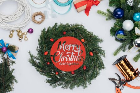 "top view of handmade christmas wreath decorations, scissors and ribbons isolated on white with ""merry christmas everyone"" lettering"