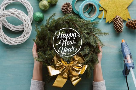 """Photo for Cropped shot of woman holding handmade pine tree wreath with golden bow and decorations on blue wooden tabletop with """"happy new year"""" lettering - Royalty Free Image"""