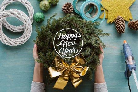 """Foto de Foto recortada de mujer sosteniendo la guirnalda de árbol de pino hecho a mano con arco oro y decoraciones en tablero de madera azul con inscripción """"feliz año nuevo"""" - Imagen libre de derechos"""