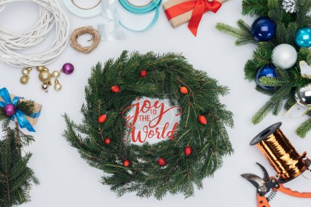 """Photo for Top view of handmade christmas wreath decorations, scissors and ribbons isolated on white with """"joy to the world"""" inspiration - Royalty Free Image"""