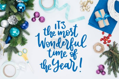 "top view of handmade christmas wreath decorations and scissors isolated on white with ""its the most wonderful time of the year"" inspiration"
