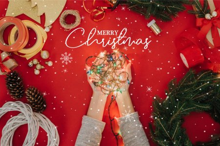 "Photo for Cropped shot of woman holding christmas lights in hands with pine tree branches and decorations for handmade wreath on red backdrop with ""merry christmas"" lettering - Royalty Free Image"