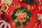 """flat lay with pine tree branches, christmas lights and ribbons for handmade christmas wreath on red backdrop with """"merry and bright"""" lettering"""