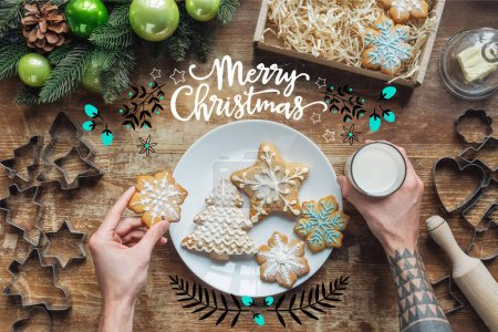 "Photo for Cropped shot of man holding homemade christmas cookie and glass of milk on wooden surface with ""merry christmas"" lettering - Royalty Free Image"