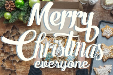 "Photo for Cropped shot of woman holding box with  homemade christmas cookies on wooden tabletop with decorative christmas wreath with ""merry christmas everyone"" lettering - Royalty Free Image"