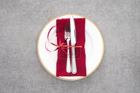 flat lay with served plate with fork and knife wrapped by red festive ribbon on grey surface