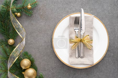 elevated view of served table with plate, fork and knife wrapped by festive ribbon near branch decorated by golden christmas balls