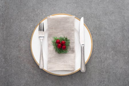 top view of served plate with fork, knife and decorated evergreen branch with christmas balls on grey surface