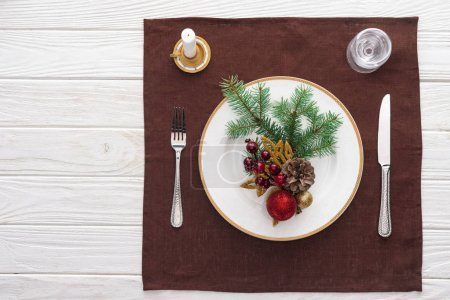 top view of served table with  wine glass, plate, fork, knife, spoon, candle and christmas decorations on tablecloth