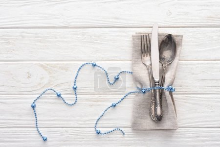 view from above of fork, knife and spoon wrapped by decorative blue beads on wooden table
