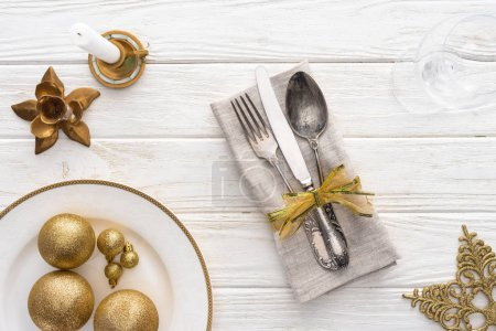 Photo for View from above of plate with golden christmas balls, candle and fork, spoon, knife wrapped by ribbon on wooden table - Royalty Free Image