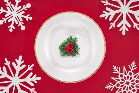 top view of plate with evergreen tree branch and christmas balls on plate surrounded by snowflakes isolated on red