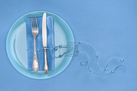Photo for View from above of fork and knife wrapped by festive beads on plate isolated on blue - Royalty Free Image